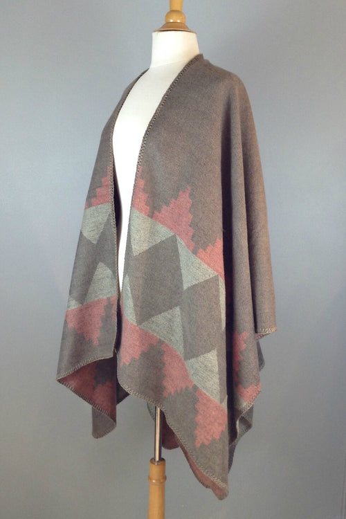 tape and dusty pink reversible poncho wrap features bold graphic print and blanket stitch detail
