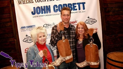 John Corbett in Las Vegas with Tipsy Totes carrying a cowboy boot tote.