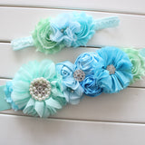 A floral maternity sash in various shades of blue and soft green with a matching mommy & me little girls head band