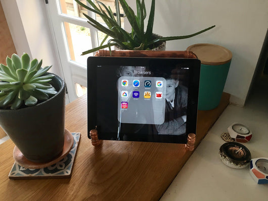 Copper Pipe iPad Stand resting on a worktop next to a cactus