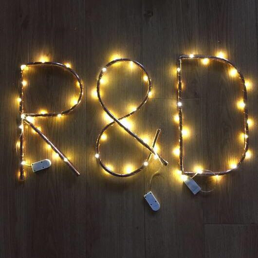 "Copper pipe letters ""R&D"" with fairy lights"
