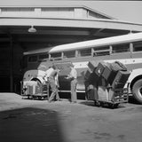 1943 Cincinnati, Ohio. Loading baggage on to a Greyhound bus  H13