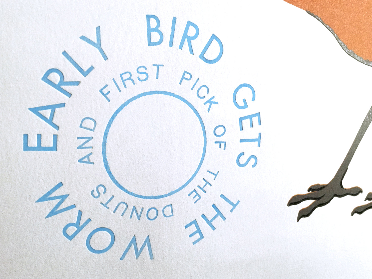 "detail of the text that reads: EARLY BIRD GETS THE WORM AND FIRST PICK OF THE DONUTS"" the detail also shows the impression the text made in to the soft paper it was printed on"