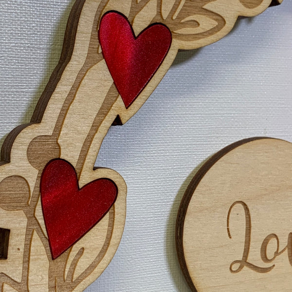 Close up of wooden wreath inlaid with red acrylic hearts - The Bespoke Workshop