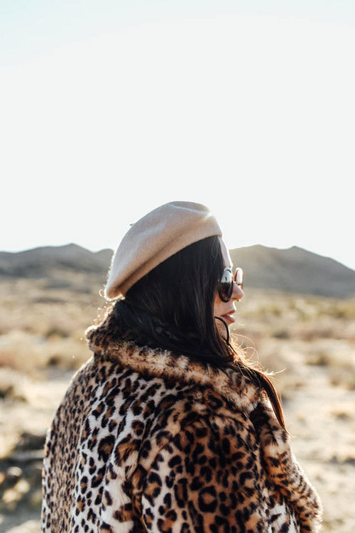 a dark-haired model wearing an animal print jacket in the desert