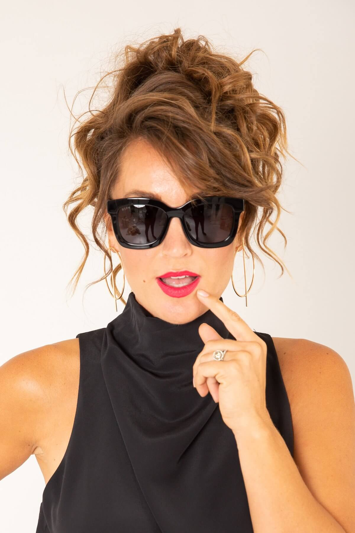 a woman with brown curly hair wearing black sunglasses
