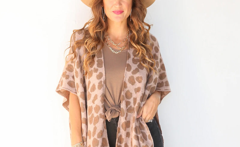 A woman wearing a cozy animal print cardigan