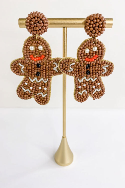 two gingerbread-shaped earrings hanging on a gold stand
