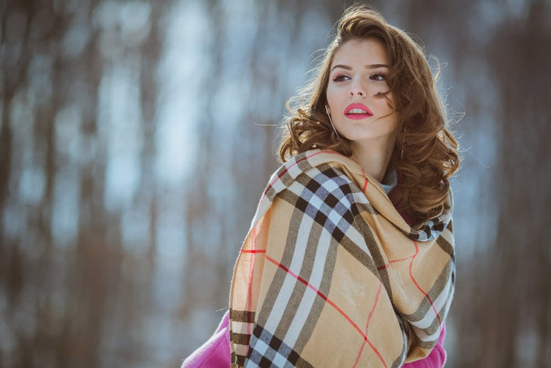 a girl with elegantly curled hair wearing a fashionable winter scarf