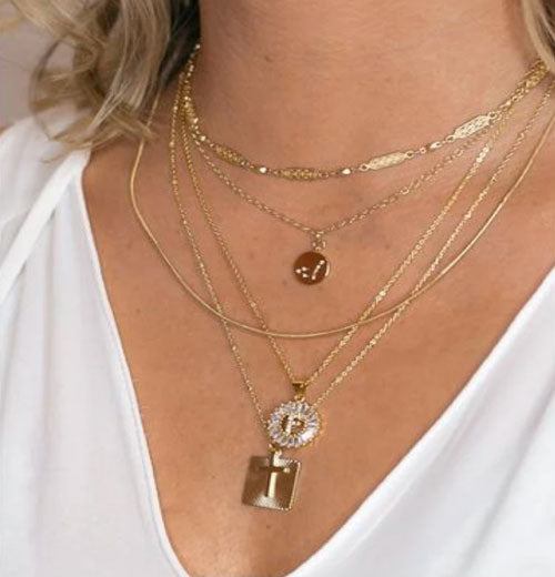 close up of woman wearing layered gold necklaces