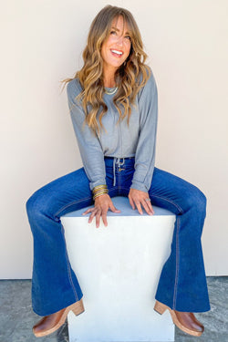 a brunette model wearing a grey long sleeve top and bell bottom jeans