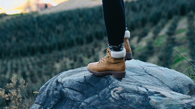 a woman's feet in booties standing on a rock while hiking