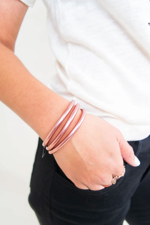 close up woman wearing rose gold bangles