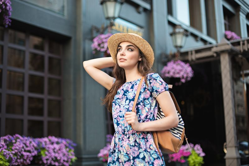 a woman in a patterned dress wearing a straw hat