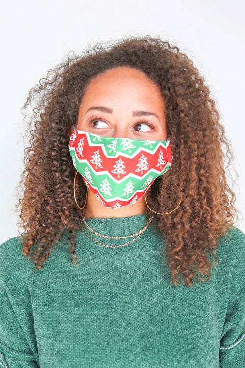 a woman wearing a face mask with a Christmas tree design