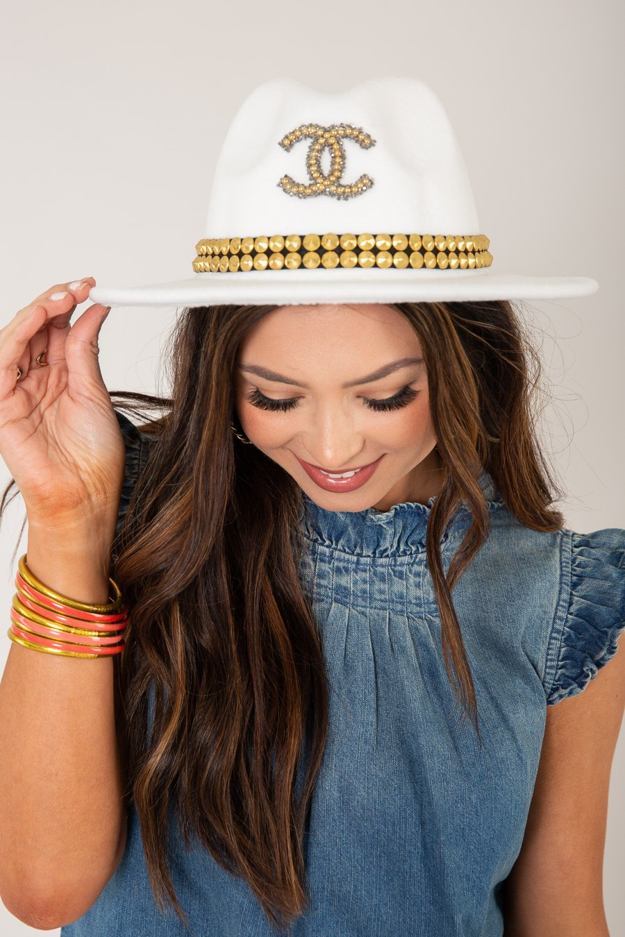 woman modeling white and gold design inspired hat
