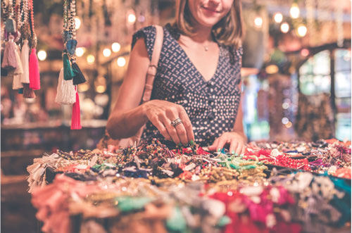 woman selecting beaded jewelry in store