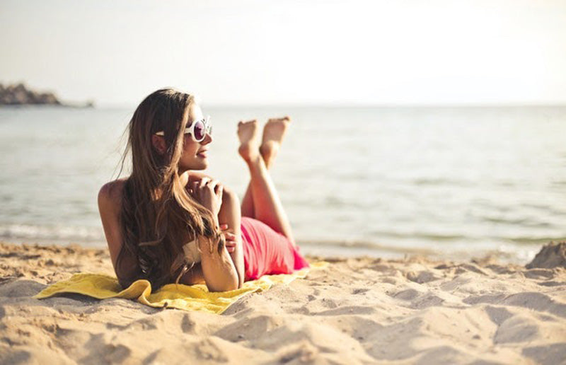 Woman smiling while lying on beach sand