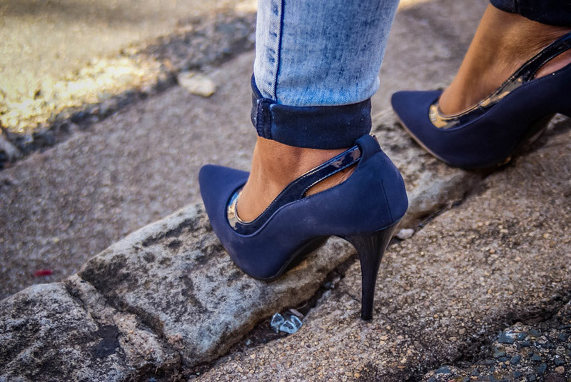 a woman's feet in blue high heel shoes on steps