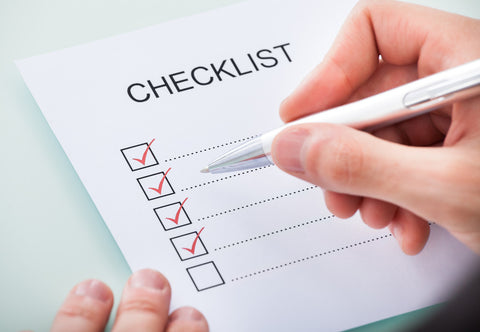 Hands hold a paper reading CHECKLIST with checked boxes