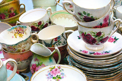 Various flowered teacups and saucers are piled together.