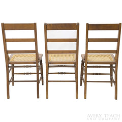 Back view of three of the American Sheraton chairs with cane seats.