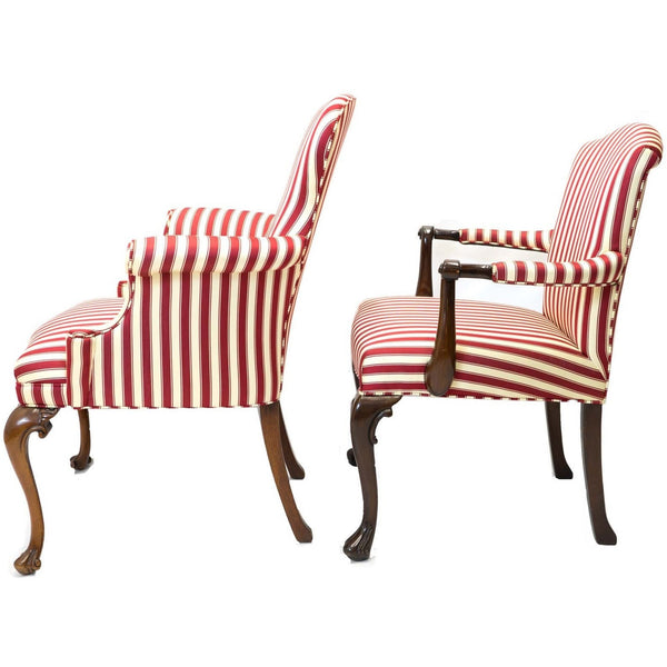 Side view of a pair of red and white striped parlor chairs.