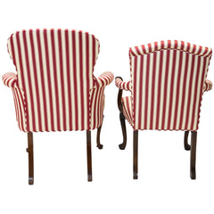 Back view of a pair of red and white striped parlor chairs.