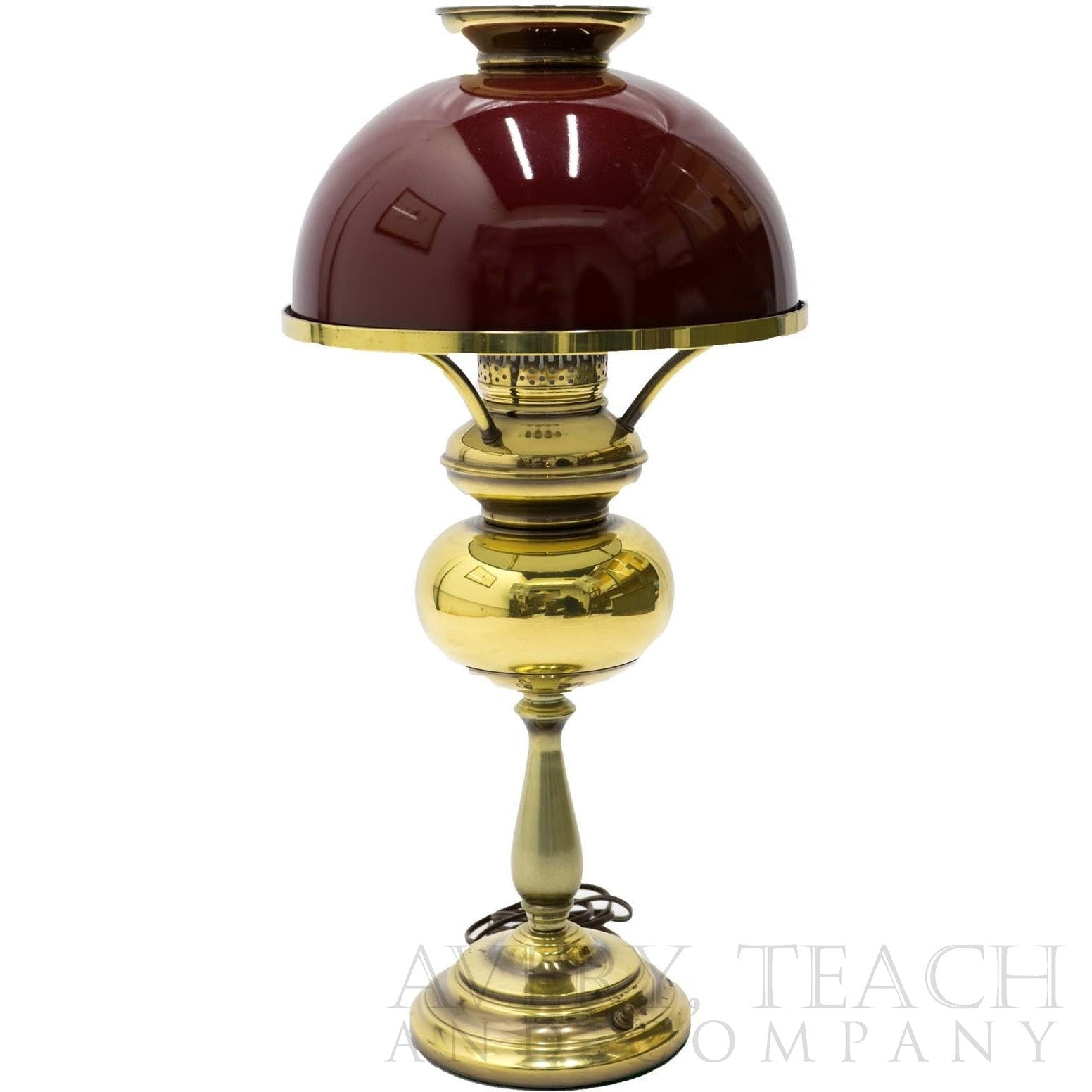 A vintage hurricane lamp with a dark red shade and golden base.