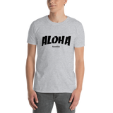 A male model wearing a Aloha Tribe Hawaii T-shirt that has Hawaii themed graphic logos on the front.