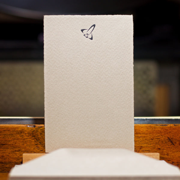 letterpress flat note card printed on italian mould-made paper with rocket ship graphic in steel gray
