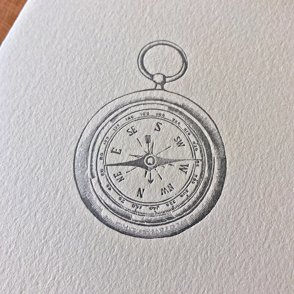 close up on compass on front of letterpress card