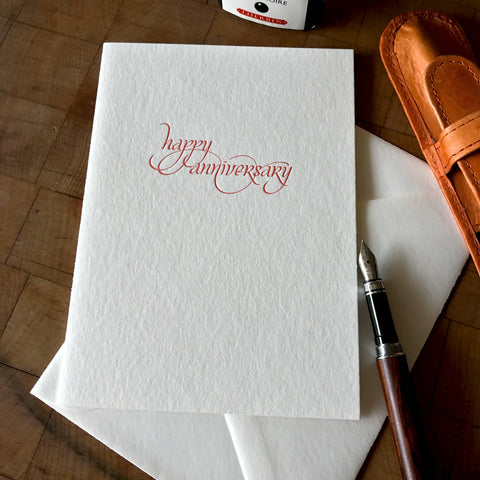 lifestyle image of happy anniversary letterpress greeting card in emberglow