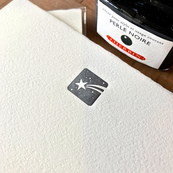 close up of shooting star letterpress letter sheet