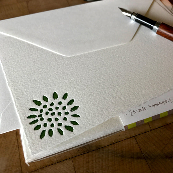 lifestyle image of sunflower letterpress flat note card in dark green