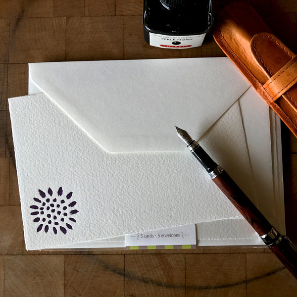 lifestyle image of sunflower letterpress flat note in dark purple