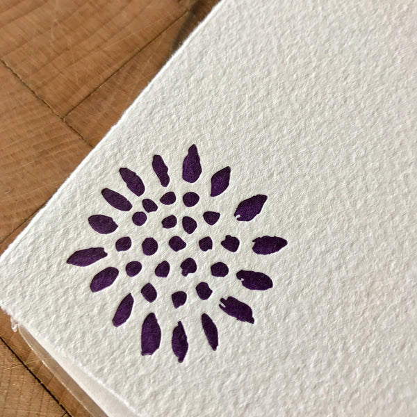 close up of sunflower letterpress flat note in dark purple