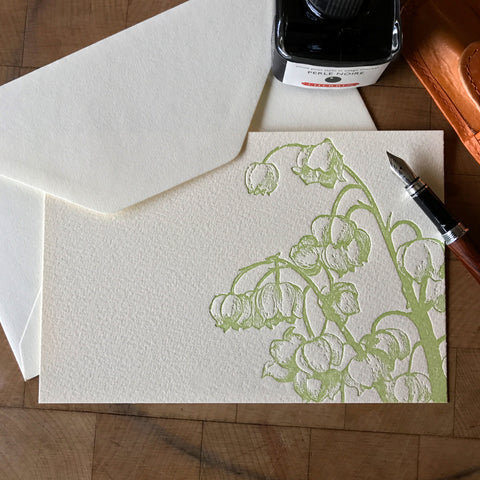 lifestyle image of lily of the valley letterpress flat note card