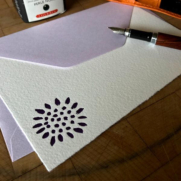 lifestyle image of sunflower letterpress flat note with lavender envelope