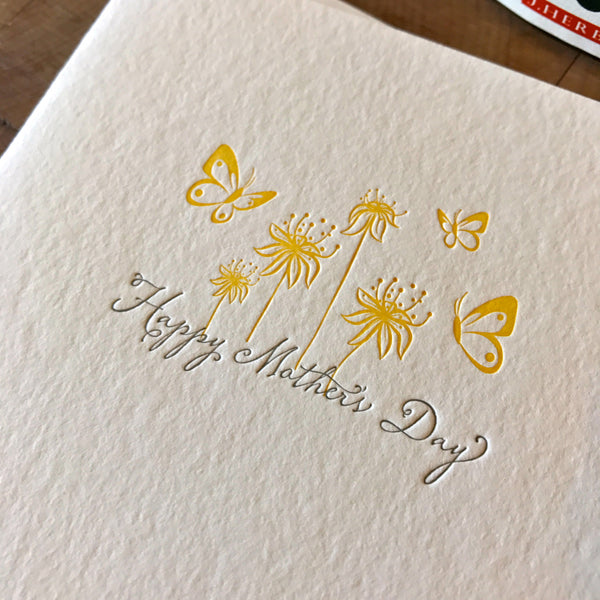 close up on happy mothers day letterpress card with butterflies