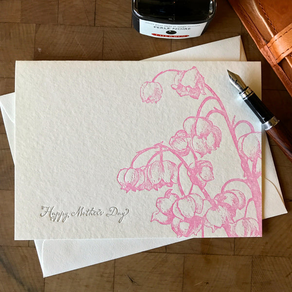 lifestyle image of happy mothers day card with pink lily of the valley