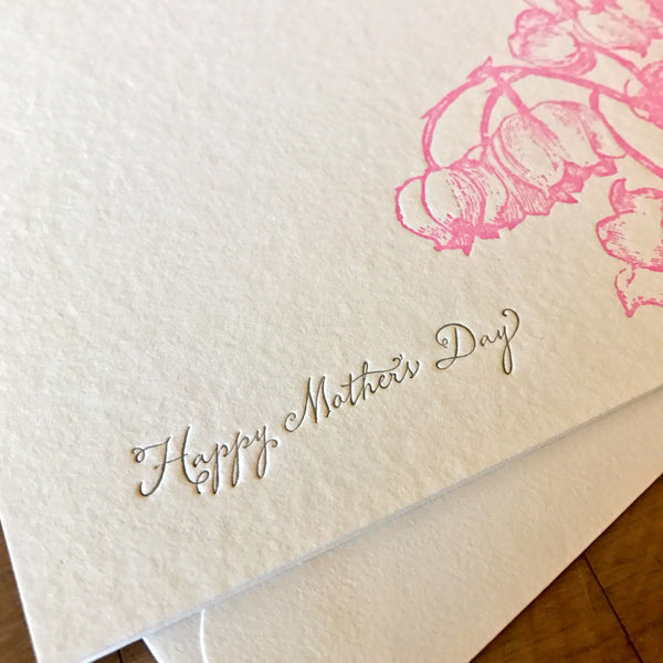 close up of happy mothers day card with pink lily of the valley