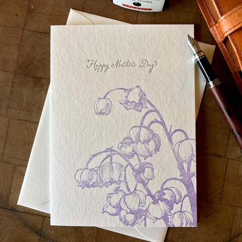 lifestyle image of happy mothers day card with lavender lily of the valley