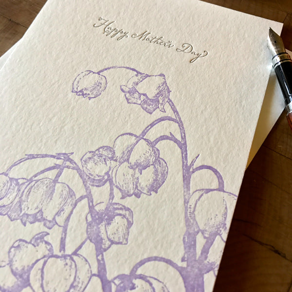 close up of happy mothers day card with lavender lily of the valley