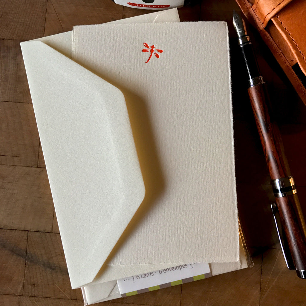 lifestyle image of dragonfly letterpress flat note card set in orange