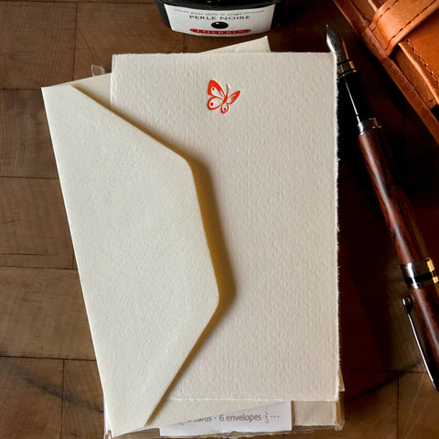 lifestyle image of butterfly letterpress flat note card in orange