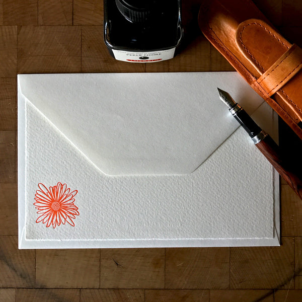 lifestyle image of string flower letterpress flat note card in tigerlily