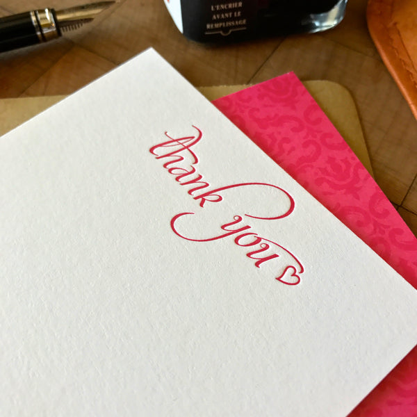 close up of thank you letterpress flat note card printed in hot pink ink with coordinating pattern imprint on reverse