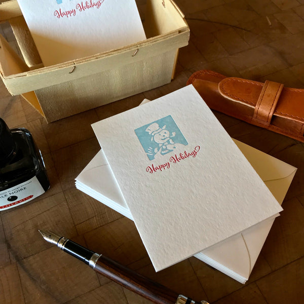 lifestyle image of happy holidays letterpress card in red pepper and sky blue