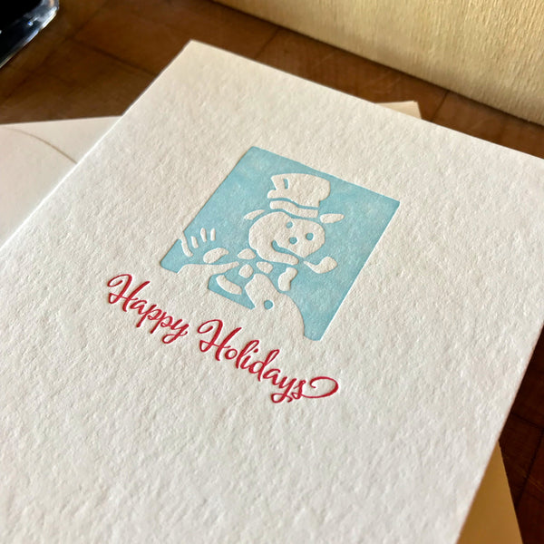 closeup of happy holidays letterpress card in red pepper and sky blue